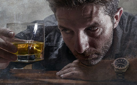 Father staring at glass of whiskey
