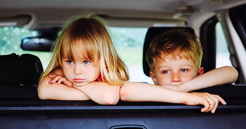 Sad children looking out the back window of a car