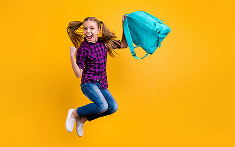 Happy girl jumping with backpack