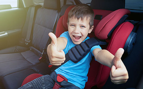 Boy in car back seat with thumbs up