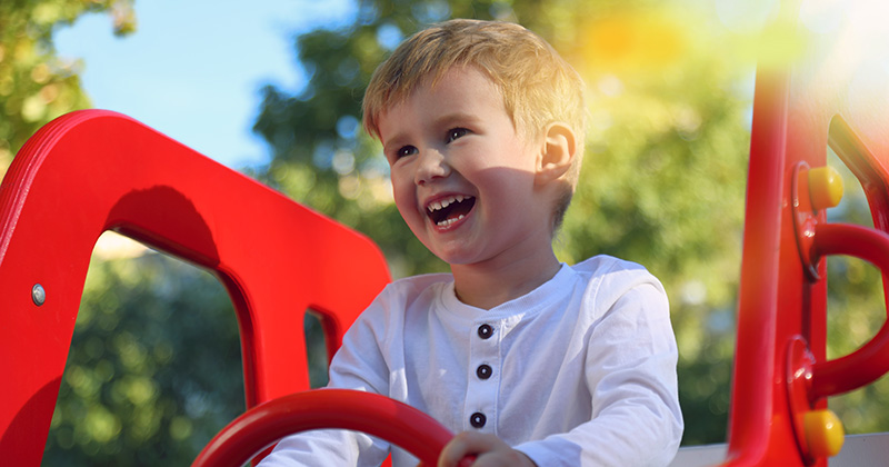 Happy toddler boy holding toy steering wheel