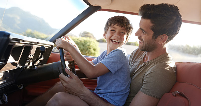 Father and son looking happy while playing in car